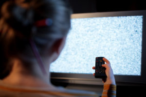 Bilde av dame som retter fjernkontroll mot tv uten signal