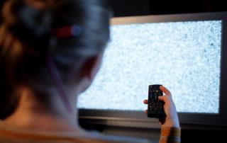 Kvinne med fjernkontroll foran tv som ikke har tv signal